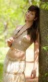 Όμορφη γυναίκα που κλίνει ενάντια στο δέντρο στοκ εικόνες