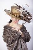 Όμορφη γυναίκα που κοιτάζει κάτω με το καπέλο φτερών, το παλτό βισώνων, και τα κόκκινα χείλια μόδα αναδρομική στοκ φωτογραφία