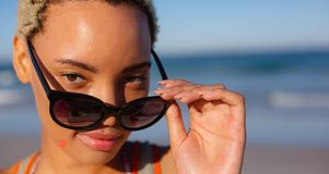 Όμορφη γυναίκα που κοιτάζει πέρα από τα γυαλιά ηλίου στην παραλία στην ηλιοφάνεια στοκ φωτογραφία