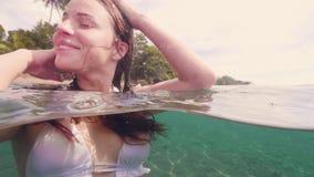 Όμορφη γυναίκα που κολυμπά στο τυρκουάζ θαλάσσιο νερό και που κοιτάζει στην άποψη ίσαλης γραμμής καμερών Γυναίκα brunette πορτρέτ φιλμ μικρού μήκους