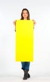Όμορφη γυναίκα που κρατά ένα κίτρινο, κενό έγγραφο Στοκ Εικόνες
