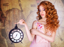 Όμορφη γυναίκα που κρατά ένα μεγάλο ρολόι Στοκ Εικόνες