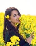 Όμορφη γυναίκα που κρατά μια δέσμη των λουλουδιών βιασμών Στοκ Εικόνες