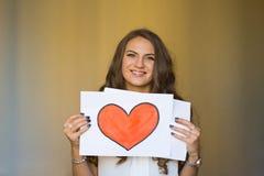 Όμορφη γυναίκα που κρατά μια ειρήνη του εγγράφου με την κόκκινη καρδιά Στοκ Εικόνες