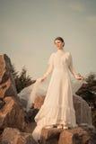 Όμορφη γυναίκα που κρατά το άσπρο μαντίλι στο υπόβαθρο ηλιοβασιλέματος Στοκ Εικόνα