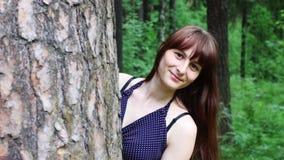 Όμορφη γυναίκα που κρυφοκοιτάζει έξω από το πίσω δέντρο στο πράσινο θερινό δάσος φιλμ μικρού μήκους