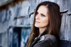 Όμορφη γυναίκα που κλίνει σε ένα κούτσουρο καμπινών Στοκ εικόνες με δικαίωμα ελεύθερης χρήσης