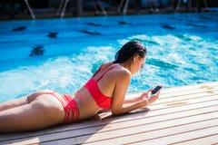 Όμορφη γυναίκα που κλίνει στο poolside και που δακτυλογραφεί ένα μήνυμα κειμένου στο κινητό τηλέφωνο στοκ φωτογραφία με δικαίωμα ελεύθερης χρήσης