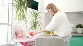 Όμορφη γυναίκα που μαγειρεύει τα υγιή τρόφιμα με το μωρό σιτηρέσιο υγιεινό φιλμ μικρού μήκους