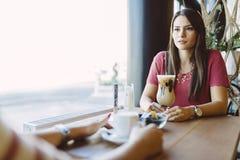 Όμορφη γυναίκα που μιλά στο φίλο στο εστιατόριο στοκ φωτογραφία