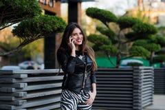 Όμορφη γυναίκα που μιλά στο κυψελοειδές τηλέφωνο υπαίθριο Στοκ Φωτογραφία