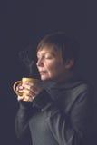 Όμορφη γυναίκα που μυρίζει τον καυτό καφέ στο σκοτεινό δωμάτιο Στοκ φωτογραφία με δικαίωμα ελεύθερης χρήσης