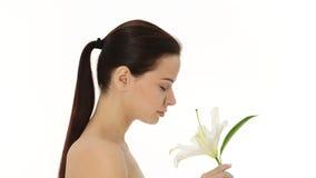 Όμορφη γυναίκα που μυρίζει το άσπρο λουλούδι. φιλμ μικρού μήκους