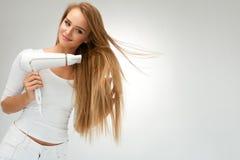 Όμορφη γυναίκα που ξεραίνει την ευθεία τρίχα που χρησιμοποιεί το στεγνωτήρα hairdressing στοκ εικόνα με δικαίωμα ελεύθερης χρήσης