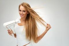 Όμορφη γυναίκα που ξεραίνει την ευθεία τρίχα που χρησιμοποιεί το στεγνωτήρα hairdressing στοκ φωτογραφία