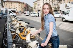 Όμορφη γυναίκα που παίρνει το ποδήλατο μισθώματος στην πόλη στοκ εικόνες