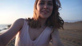 Όμορφη γυναίκα που παίρνει selfie χρησιμοποιώντας το τηλέφωνο στην παραλία στο ηλιοβασίλεμα που χαμογελά και που περιστρέφει απολ
