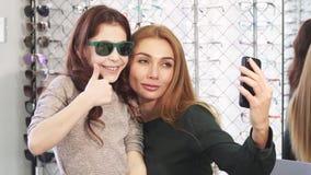 Όμορφη γυναίκα που παίρνει selfies με τη χαριτωμένη κόρη της στο eyewear κατάστημα απόθεμα βίντεο