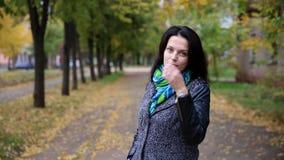 Όμορφη γυναίκα που περπατά και που γυρίζει στη κάμερα στο πάρκο HD απόθεμα βίντεο