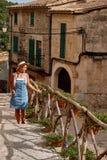 Όμορφη όμορφη γυναίκα που περπατά στην παλαιά οδό πόλης πεζοδρομίων με τα λουλούδια και που κοιτάζει μακριά μικρό ταξίδι χαρτών τ Στοκ εικόνα με δικαίωμα ελεύθερης χρήσης