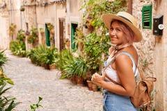 Όμορφη όμορφη γυναίκα που περπατά στην παλαιά οδό πόλης πεζοδρομίων με τα λουλούδια και που κοιτάζει μακριά μικρό ταξίδι χαρτών τ Στοκ Φωτογραφίες
