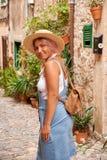 Όμορφη όμορφη γυναίκα που περπατά στην παλαιά οδό πόλης πεζοδρομίων με τα λουλούδια και που κοιτάζει μακριά μικρό ταξίδι χαρτών τ Στοκ φωτογραφίες με δικαίωμα ελεύθερης χρήσης
