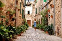 Όμορφη όμορφη γυναίκα που περπατά στην παλαιά οδό πόλης πεζοδρομίων με τα λουλούδια και που κοιτάζει μακριά μικρό ταξίδι χαρτών τ Στοκ Εικόνες