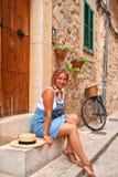 Όμορφη όμορφη γυναίκα που περπατά στην παλαιά οδό πόλης πεζοδρομίων με τα λουλούδια και που κοιτάζει μακριά μικρό ταξίδι χαρτών τ Στοκ Εικόνα