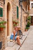 Όμορφη όμορφη γυναίκα που περπατά στην παλαιά οδό πόλης πεζοδρομίων με τα λουλούδια και που κοιτάζει μακριά μικρό ταξίδι χαρτών τ Στοκ Φωτογραφία