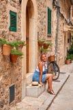 Όμορφη όμορφη γυναίκα που περπατά στην παλαιά οδό πόλης πεζοδρομίων με τα λουλούδια και που κοιτάζει μακριά μικρό ταξίδι χαρτών τ Στοκ φωτογραφία με δικαίωμα ελεύθερης χρήσης