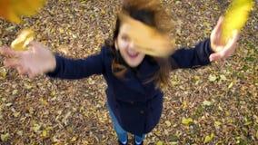 Όμορφη γυναίκα που πηδά επάνω ευτυχώς να πετάξει το κίτρινο φύλλωμα 4k 60fps σε αργή κίνηση Κορίτσι σε ένα παλτό που περπατά το φ φιλμ μικρού μήκους