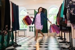 Όμορφη γυναίκα που πηδά επάνω με τις συσκευασίες στο κατάστημα ιματισμού στοκ εικόνα