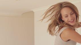 Όμορφη γυναίκα που πηδά στο κρεβάτι απόθεμα βίντεο