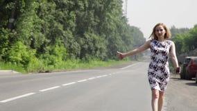 Όμορφη γυναίκα που πιάνει το αυτοκίνητο σε έναν δρόμο Κορίτσι που περπατά κατά μήκος του δρόμου απόθεμα βίντεο