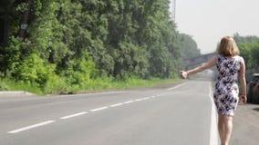 Όμορφη γυναίκα που πιάνει το αυτοκίνητο σε έναν δρόμο Κορίτσι που περπατά κατά μήκος του δρόμου φιλμ μικρού μήκους