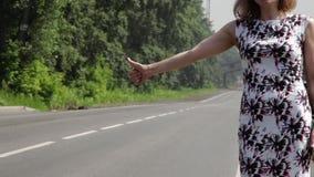 Όμορφη γυναίκα που πιάνει το αυτοκίνητο σε έναν δρόμο απόθεμα βίντεο