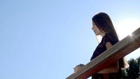 Όμορφη γυναίκα που στέκεται και που κλίνει στα κιγκλιδώματα στο μπαλκόνι απόθεμα βίντεο