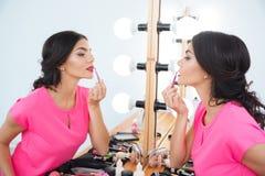 Όμορφη γυναίκα που στέκεται κοντά στον καθρέφτη και που βάζει στο κόκκινο κραγιόν Στοκ Εικόνες