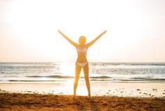Όμορφη γυναίκα που στέκεται μπροστά από το ηλιοβασίλεμα στην παραλία Στοκ Εικόνες