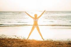 Όμορφη γυναίκα που στέκεται μπροστά από το ηλιοβασίλεμα στην παραλία Στοκ Φωτογραφίες