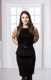 Όμορφη γυναίκα που στέκεται σε ένα μαύρο φόρεμα πέρα από τις εγχώριες εσωτερικές πόρτες σοφιτών στούντιο πίσω στοκ φωτογραφίες