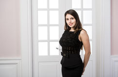 Όμορφη γυναίκα που στέκεται σε ένα μαύρο φόρεμα πέρα από τις εγχώριες εσωτερικές πόρτες σοφιτών στούντιο πίσω στοκ εικόνα
