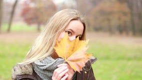 Όμορφη γυναίκα που στέλνει το φιλί, που κρατά το φύλλο στο χέρι της απόθεμα βίντεο