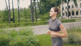 Όμορφη γυναίκα που τρέχει στο σκούντημα πρωινού η καρδιο κατάρτιση υπαίθρια απόθεμα βίντεο