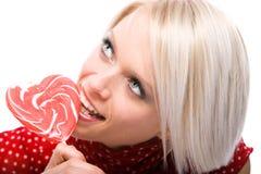Όμορφη γυναίκα που τρώει καρδιά-διαμορφωμένη lollipop Στοκ εικόνα με δικαίωμα ελεύθερης χρήσης