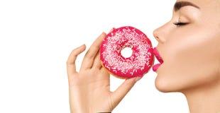Όμορφη γυναίκα που τρώει ρόδινο doughnut στοκ φωτογραφίες