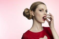 Όμορφη γυναίκα που τρώει την πραλίνα στοκ φωτογραφίες