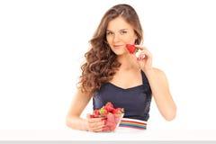 Όμορφη γυναίκα που τρώει τις φράουλες Στοκ Εικόνες