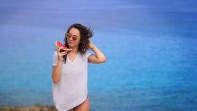 Όμορφη γυναίκα που τρώει το καρπούζι στην παραλία θάλασσας Απολαύστε τις διακοπές ευτυχές καλοκαίρι απόθεμα βίντεο