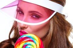 Όμορφη γυναίκα που τρώει το μεγάλο κόκκινο lollipop στο καπέλο ήλιων Στοκ Φωτογραφίες